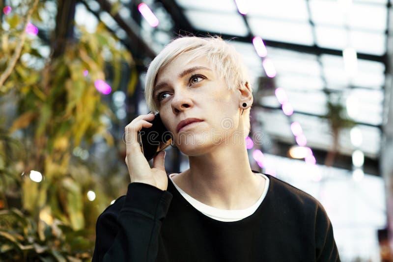 Retrato da mulher do moderno com cabelo curto louro que fala pelo telefone celular imagens de stock royalty free