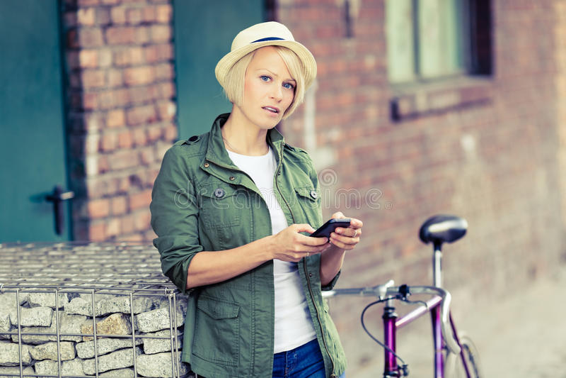 Retrato da mulher do moderno com telefone e bicicleta fotografia de stock royalty free