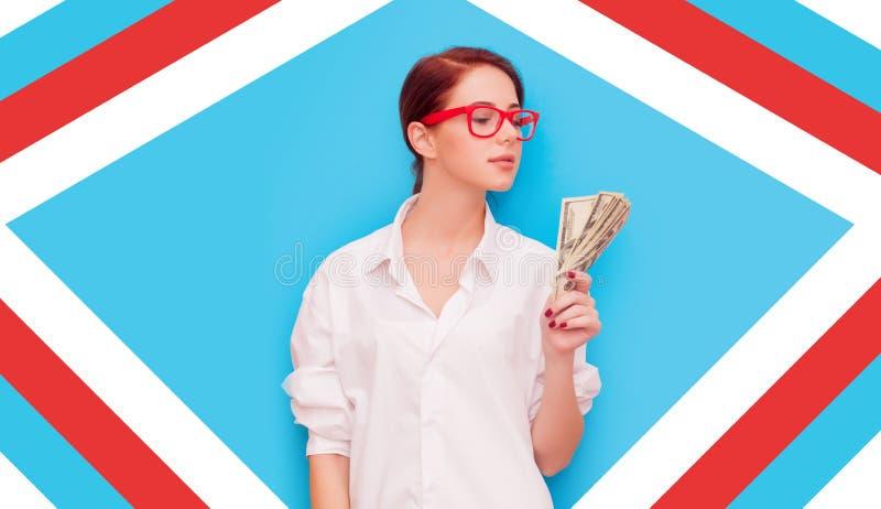Retrato da mulher do ruivo em vidros vermelhos com dinheiro fotografia de stock royalty free