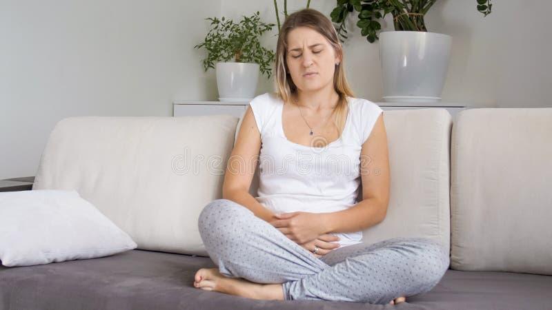Retrato da mulher doente nova que sofre da dor abdominal fotografia de stock