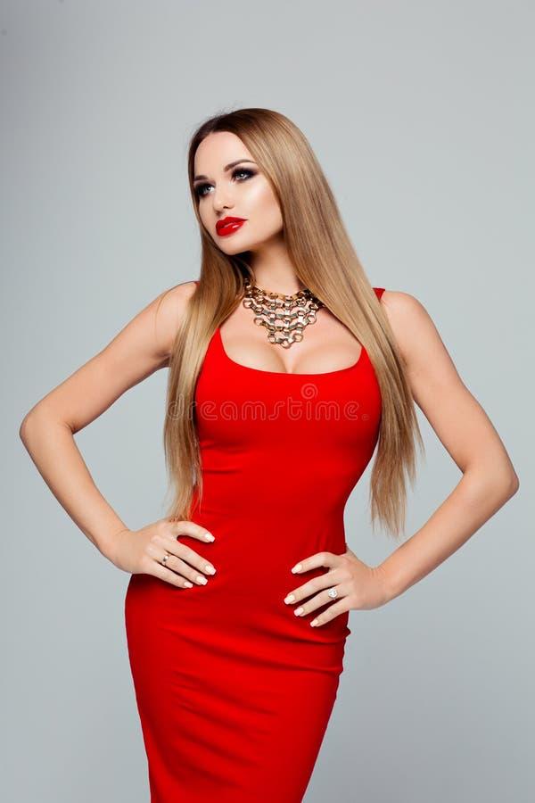 Retrato da mulher elegante bonita em um vestido vermelho brilhante com uma colar do ouro e uns bordos vermelhos Menina delgada co imagem de stock royalty free
