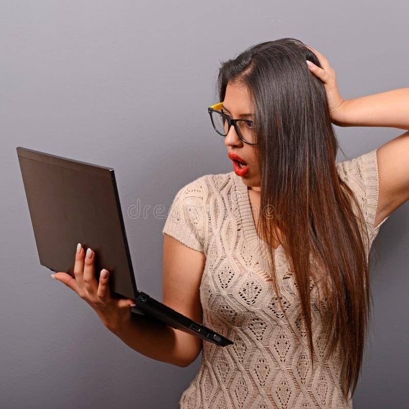 Retrato da mulher em choque o que vê em seu portátil contra o fundo cinzento imagens de stock royalty free