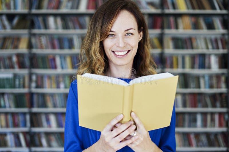 Retrato da mulher em uma biblioteca com realizar aberto nas mãos, cabelo longo do livro Menina nova da estudante universitário no imagem de stock royalty free