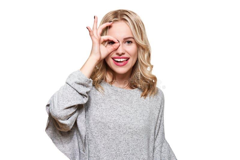 Retrato da mulher entusiasmado bonita na roupa ocasional que sorri e que mostra o sinal aprovado na câmera isolada sobre o branco imagem de stock