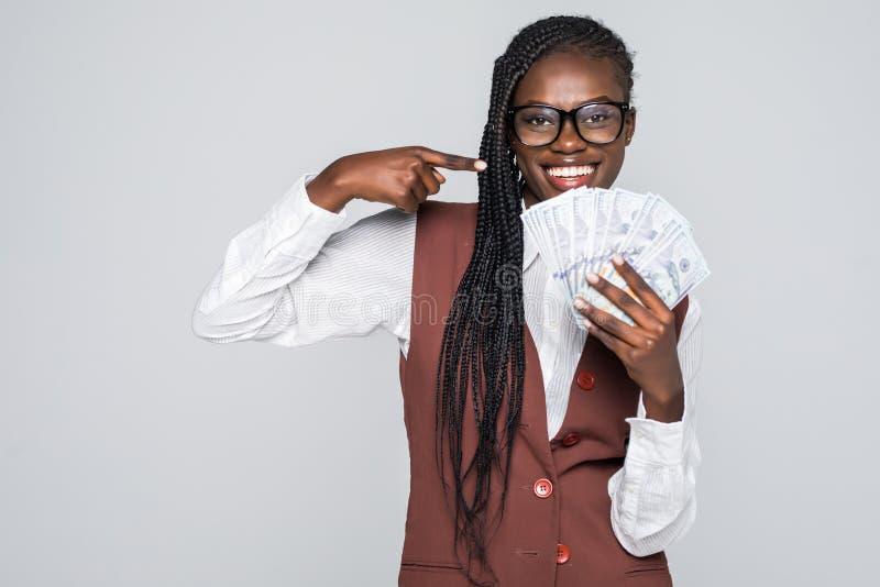Retrato da mulher entusiasmado com apontar o dedo no fã das notas de dólar do dinheiro isoladas sobre o fundo cinzento fotografia de stock royalty free