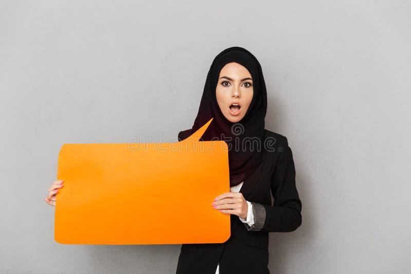 Retrato da mulher entusiasmado muçulmana 20s no hijab preto que olha c imagem de stock royalty free