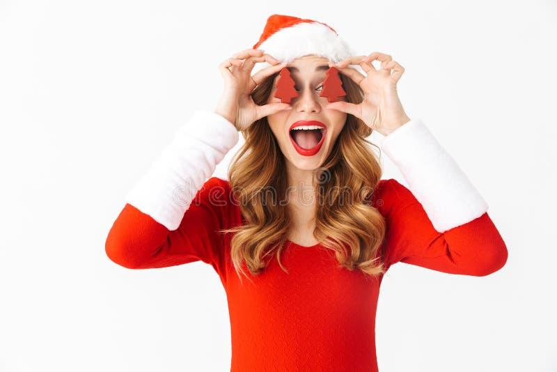 Retrato da mulher entusiasmado 20s que veste o traje vermelho de Santa Claus que sorri e que guarda decorações do Natal, isolado  imagens de stock royalty free