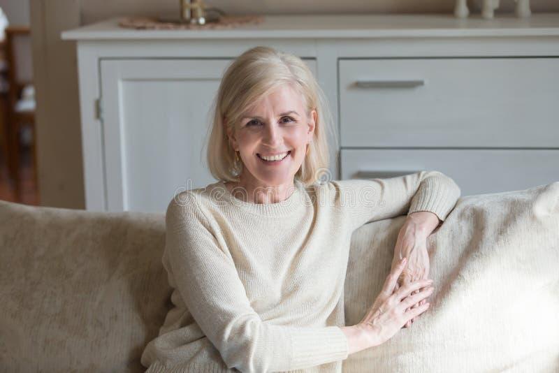 Retrato da mulher envelhecida de sorriso que relaxa no sofá acolhedor fotos de stock