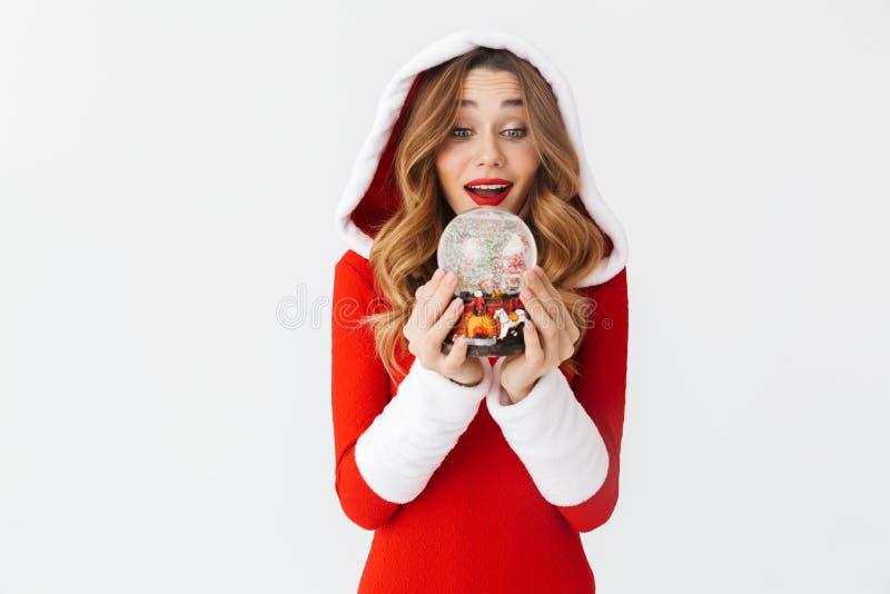 Retrato da mulher europeia 20s que veste o traje vermelho de Santa Claus que sorri e que guarda a bola da neve do Natal, isolado  imagem de stock royalty free