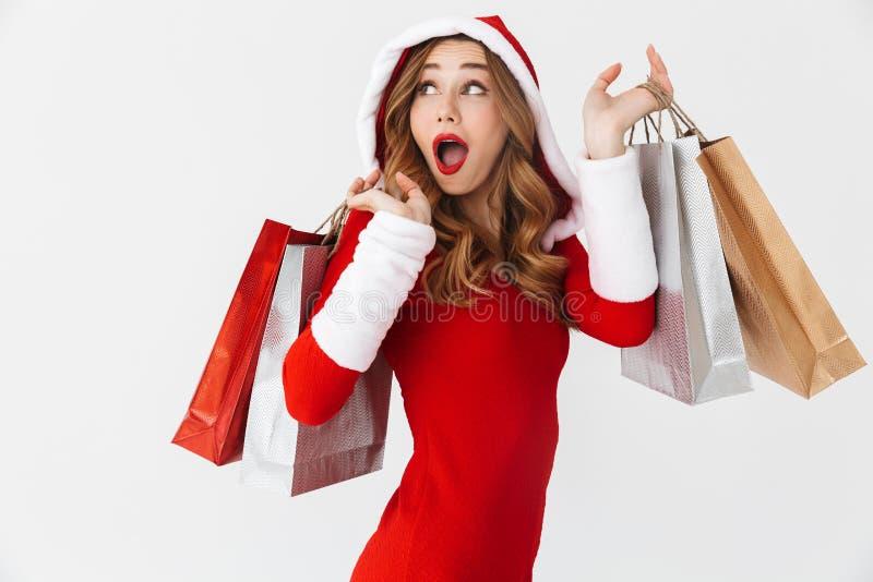 Retrato da mulher europeia 20s que veste o traje vermelho de Santa Claus que sorri e que guarda sacos de compras de papel colorid fotografia de stock