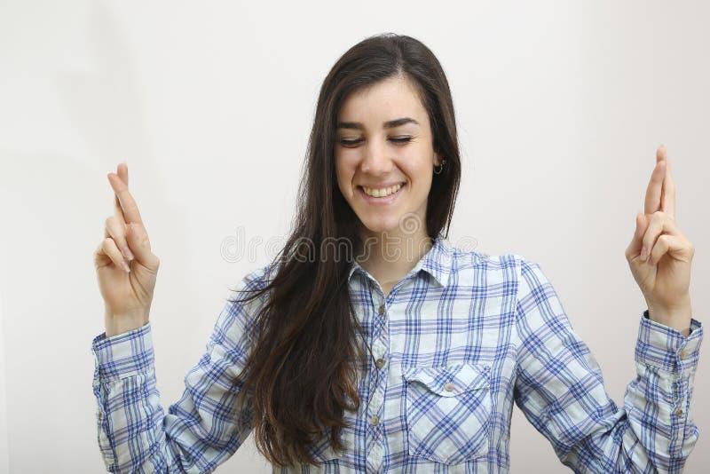 Retrato da mulher feliz com os dedos cruzados fotos de stock royalty free