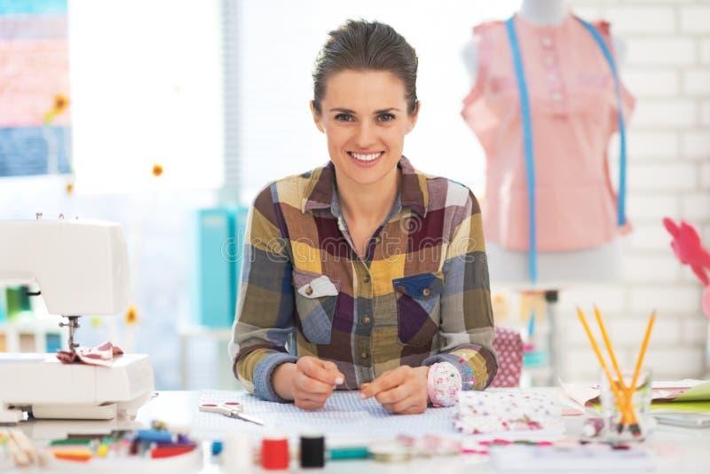 Retrato da mulher feliz da costureira no trabalho imagem de stock
