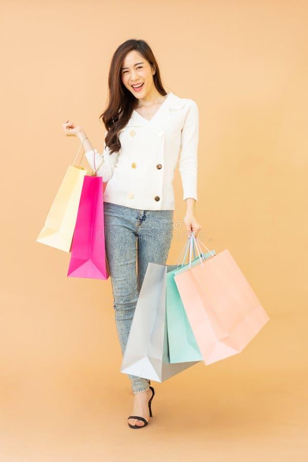 Retrato da mulher feliz de sorriso nova bonita que guarda o fundo alaranjado isolado sacos de compras imagens de stock