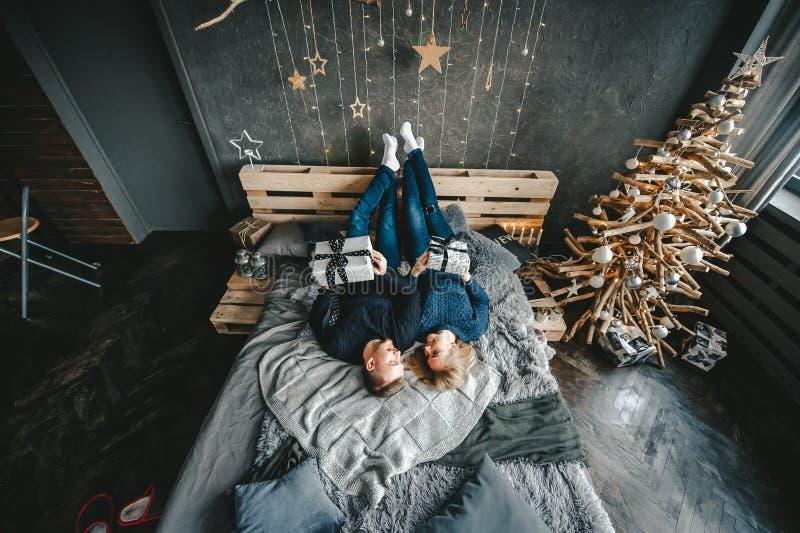 Retrato da mulher feliz e do homem que encontram-se na cama que descansa junto em casa Vista superior imagens de stock