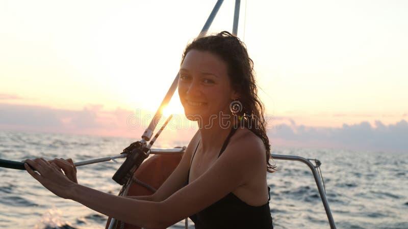 Retrato da mulher feliz no roupa de banho em um iate e em apreciar uma opinião do mar no por do sol foto de stock royalty free