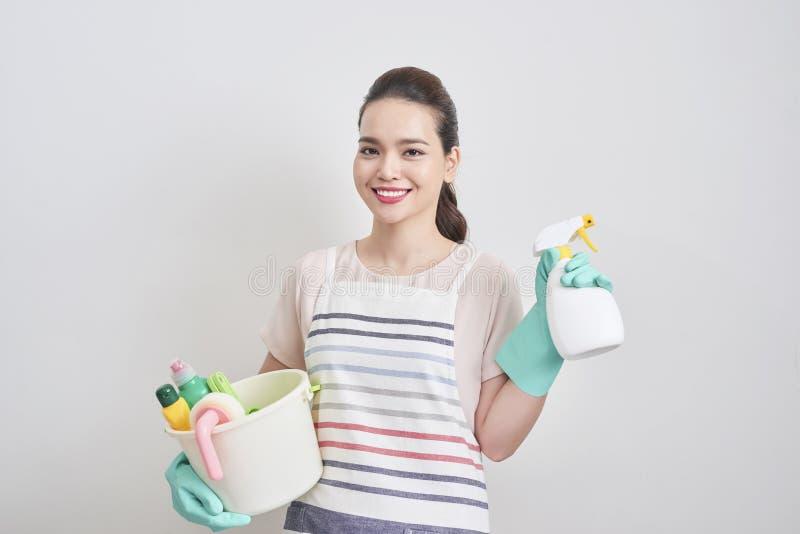 Retrato da mulher feliz que realiza em seus produtos de limpeza w das mãos imagens de stock