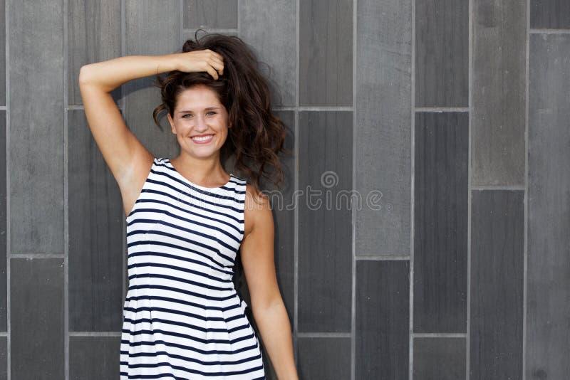 Retrato da mulher feliz que sorri com mão no cabelo fotografia de stock