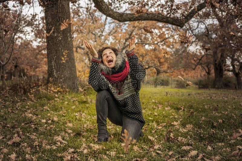 Retrato da mulher feliz que tem o divertimento com as folhas no outono imagens de stock royalty free