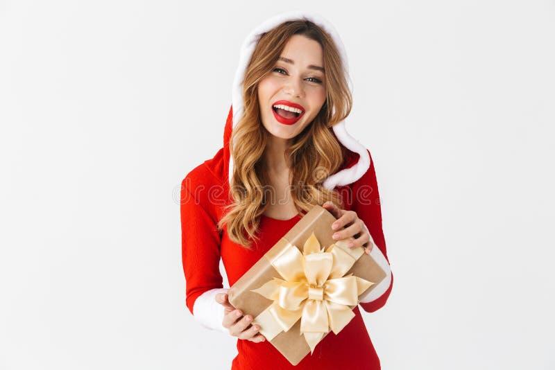Retrato da mulher feliz 20s que veste o traje vermelho de Santa Claus que sorri e que guarda a caixa atual, isolado sobre o fundo fotografia de stock