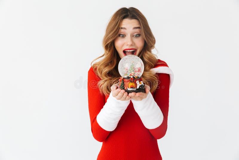 Retrato da mulher festiva 20s que veste o traje vermelho de Santa Claus que sorri e que guarda a bola da neve do Natal, isolado s fotografia de stock royalty free