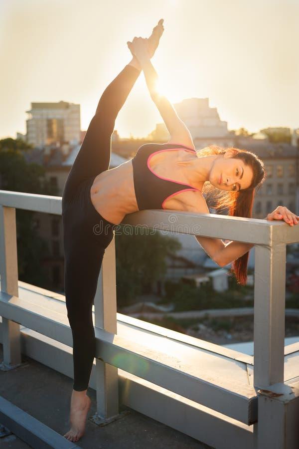 Retrato da mulher forte bonita no sportwear que faz o exerc?cio da ioga do exerc?cio e que estica no fundo urbano Desportivo f?me foto de stock