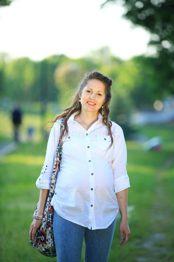 Retrato da mulher gravida bonita com um saco em seu ombro imagens de stock royalty free