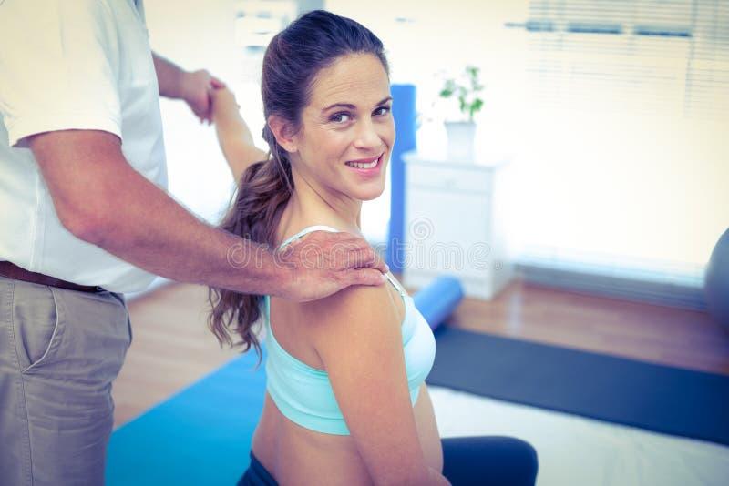Retrato da mulher gravida que recebe a massagem imagem de stock