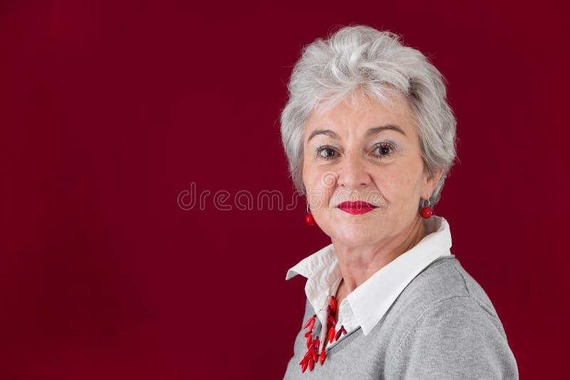 Retrato da mulher idosa séria em vermelho e em cinzento imagens de stock royalty free