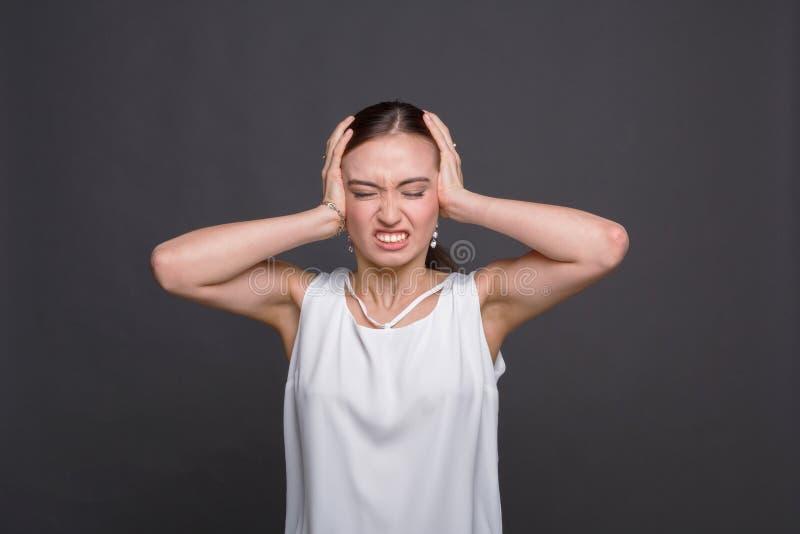 Retrato da mulher irritada que guarda sua cabeça foto de stock