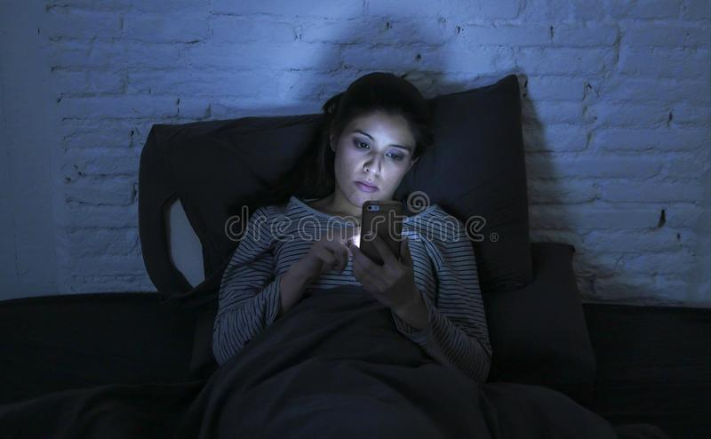 Retrato da mulher latin bonita nova que usa o encontro sem sono tardio do telefone celular na cama na obscuridade no smartphone e fotografia de stock