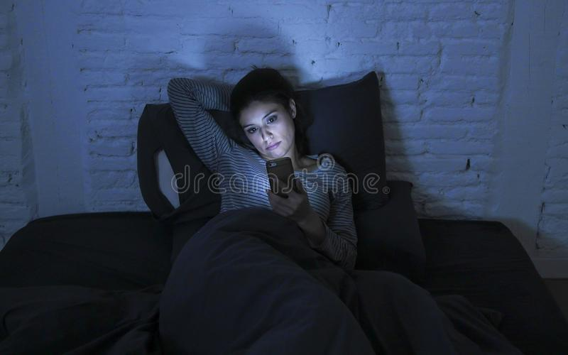 Retrato da mulher latin bonita nova que usa o encontro sem sono tardio do telefone celular na cama na obscuridade no smartphone e fotos de stock