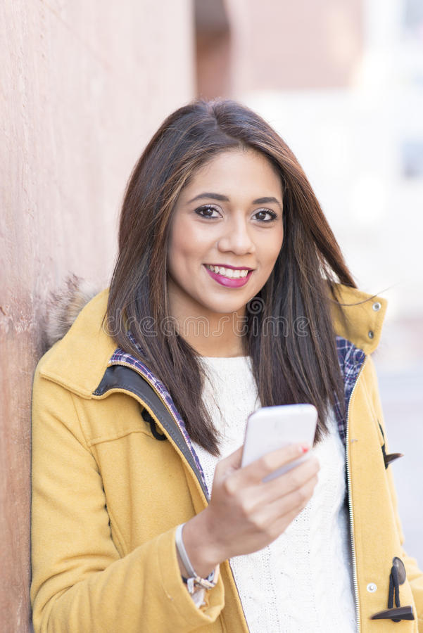 Retrato da mulher latin da felicidade bonita que guarda o telefone e o lo foto de stock