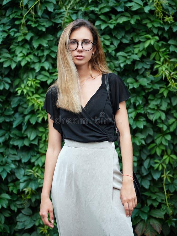 Retrato da mulher longa bonita nova do cabelo que veste a blusa preta, levantando no parque do verde do verão contra o fundo da h imagens de stock