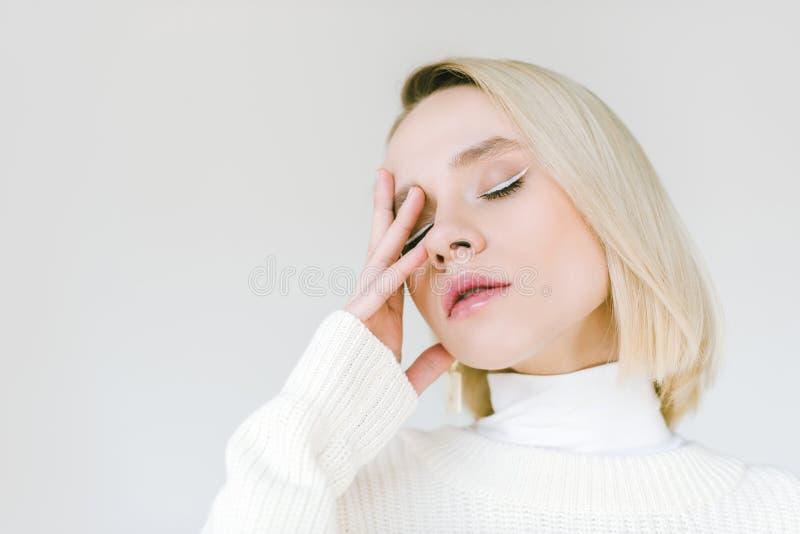 retrato da mulher loura à moda bonita na roupa branca que toca na cara com mão fotos de stock