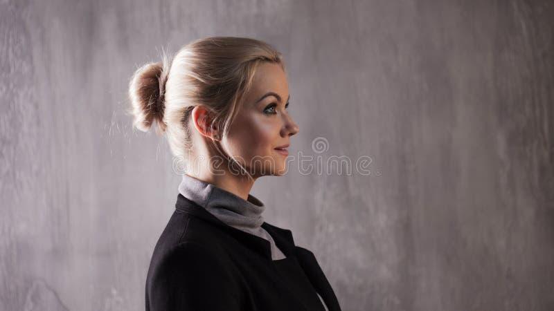 Retrato da mulher loura bonita Calma e autoconfiança Menina adulta bonita na gola alta preta, fundo cinzento imagens de stock