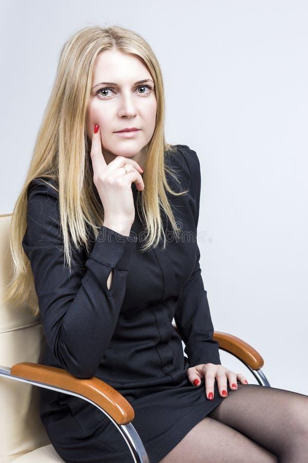 Retrato da mulher loura calma que senta-se na cadeira clara Tiro do estúdio imagem de stock royalty free