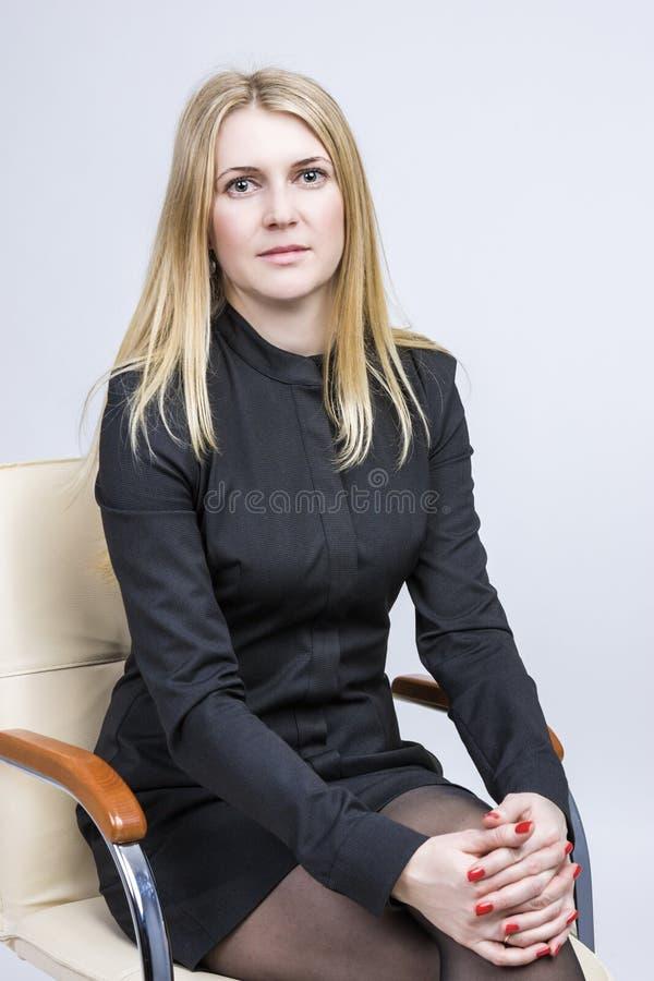 Retrato da mulher loura calma que senta-se na cadeira clara Tiro do estúdio foto de stock
