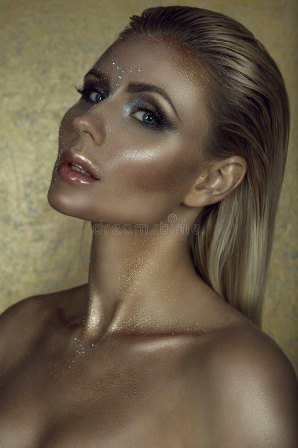 Retrato da mulher loura chique lindo com cabelo molhado, os bordos completos partidos e composição artística de brilho fotografia de stock