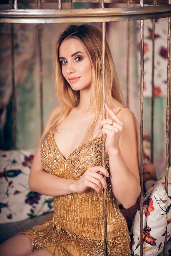 Retrato da mulher loura de sorriso atrativa no vestido dourado curto no estúdio foto de stock