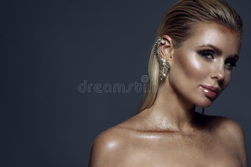 Retrato da mulher loura lindo chique com cabelo molhado, composição de brilho artística e o punho em sua orelha foto de stock