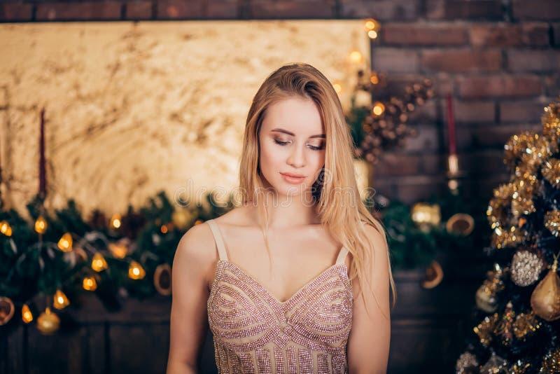 Retrato da mulher loura luxuoso no vestido de nivelamento dourado na árvore de Natal e nas velas do fundo fotos de stock royalty free