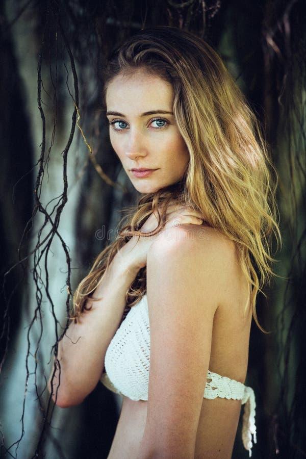 Retrato da mulher loura nova bonita com olhos azuis e composição natural no sutiã branco vestindo do biquini da selva tropical da imagem de stock royalty free