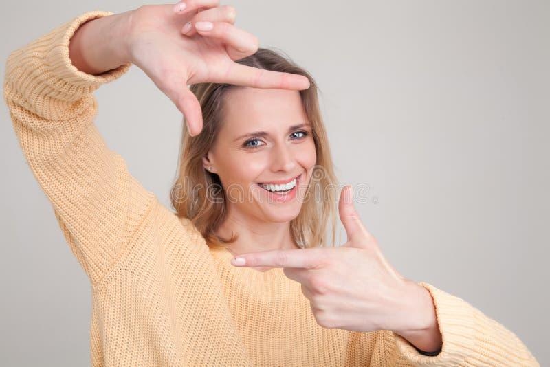 Retrato da mulher loura nova com express?o feliz alegre em sua cara, com o bom humor, fazendo o quadrado com seus dedos desgastar fotos de stock royalty free