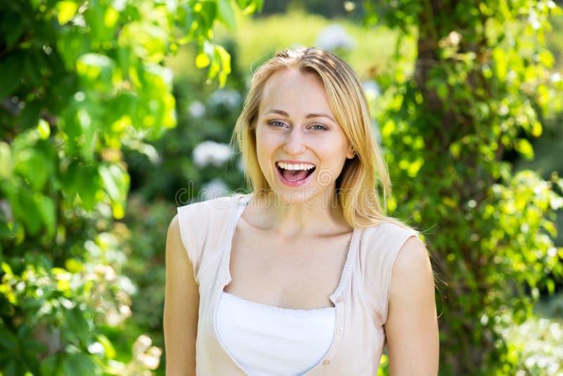 Retrato da mulher loura nova contente no jardim fotografia de stock royalty free