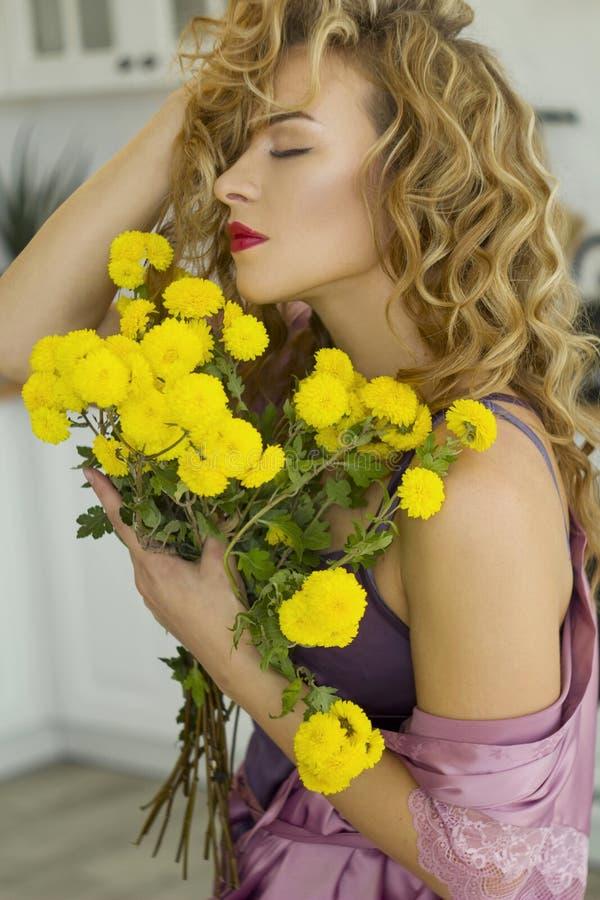 Retrato da mulher loura nova na sala de visitas brilhante que guarda flores amarelas imagens de stock