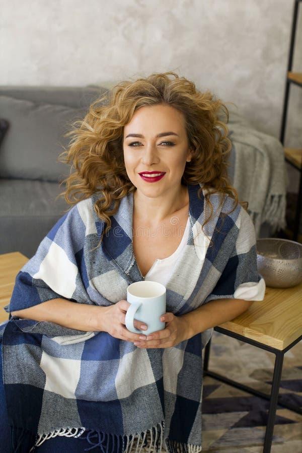 Retrato da mulher loura nova no copo bebendo da sala de visitas brilhante do chá ou do café fotos de stock