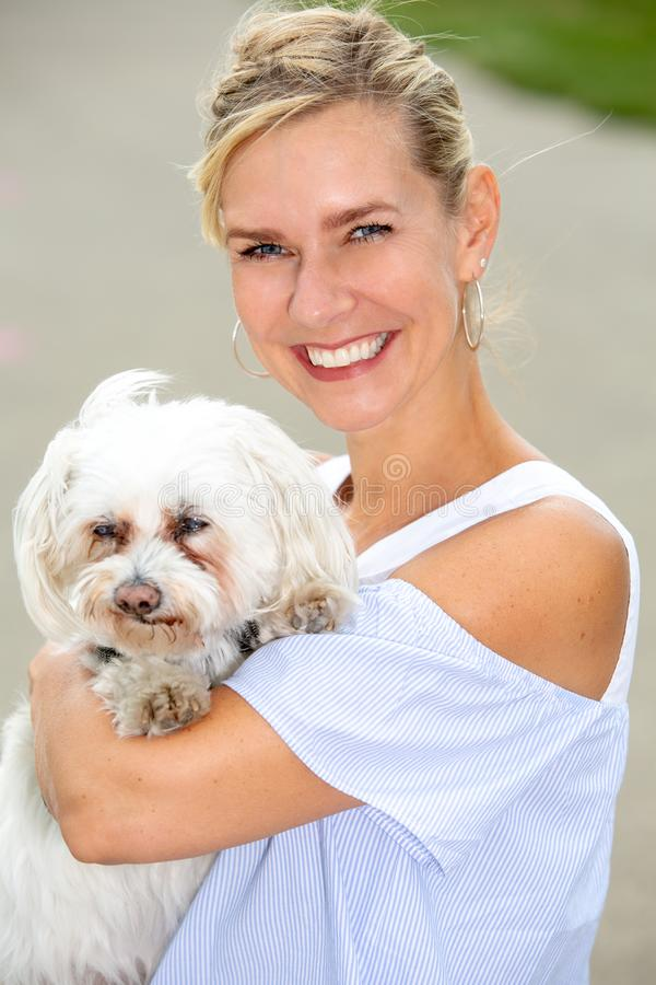 Retrato da mulher loura que guarda um cão branco pequeno bonito fotos de stock