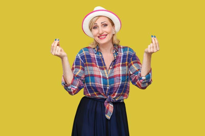 Retrato da mulher madura à moda moderna engraçada no estilo ocasional com posição do chapéu com gesto do dinheiro ou do italiano  imagem de stock