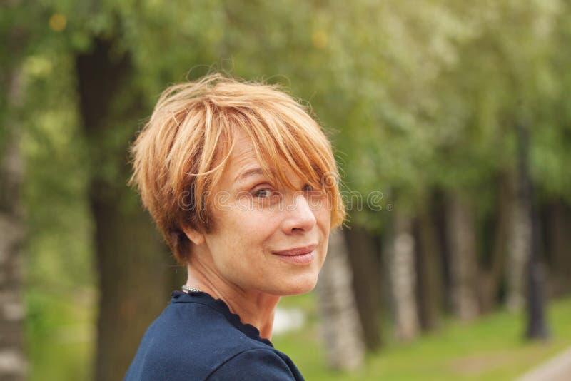Retrato da mulher madura bonita com ar livre curto vermelho elegante do corte de cabelo foto de stock