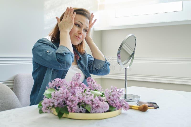 Retrato da mulher madura com espelho da composi??o que faz massagens seus cara e pesco?o, f?mea bonita 40 anos velha fotografia de stock